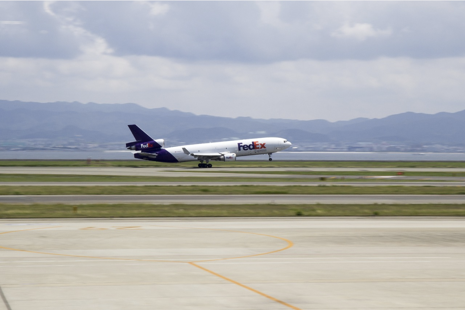 A air plane with the FedEx branding is taking off from the runway