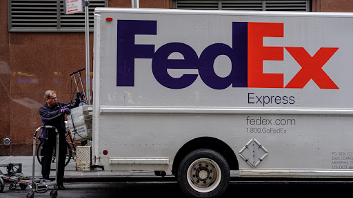 A person loading shipment in a Fedex branded van