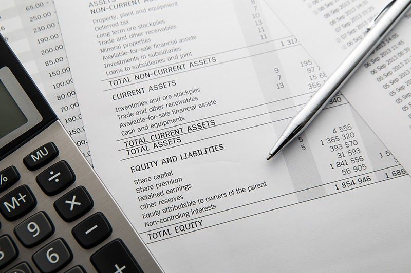 Pen and calculator kept on top of a balance sheet